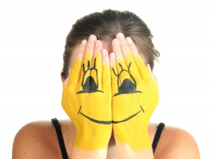 Portrait of girl hiding her face under smile mask isolated on wh
