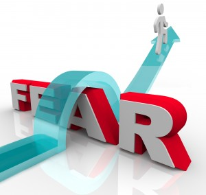 bigstock-A-man-jumps-over-the-word-fear-061813